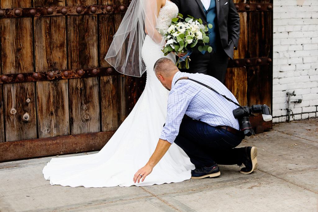 Wedding Photographer fixing dress downtown